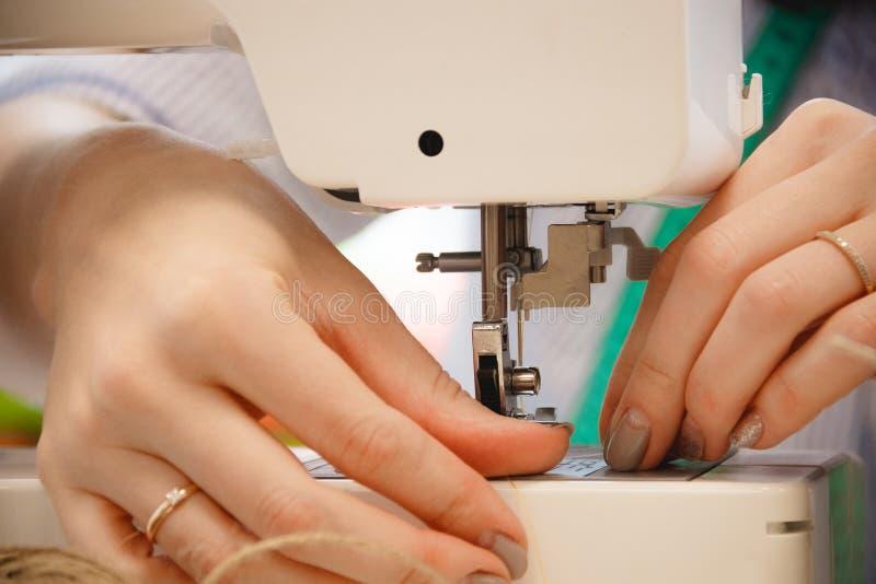 Frauennäherinarbeit über Nähmaschine stockfotos