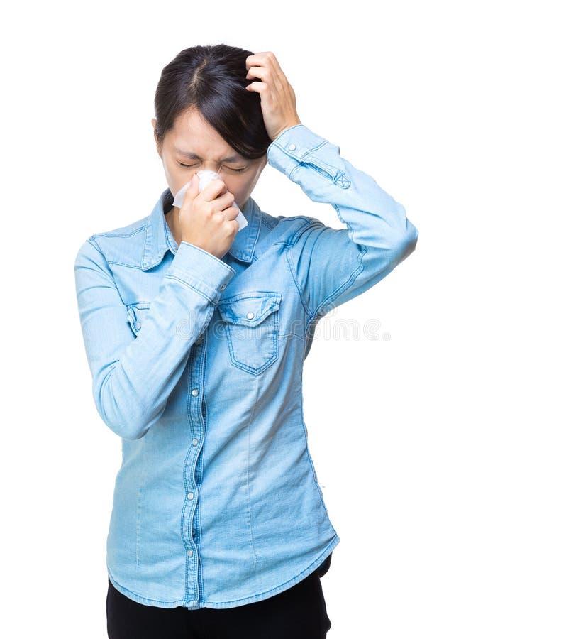 Frauenniesen und -kopfschmerzen stockfoto