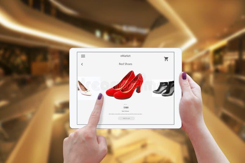 Frauenon-line-Einkaufen mit Tablette Holdinggerät und wählen rote Schuhe stockfoto