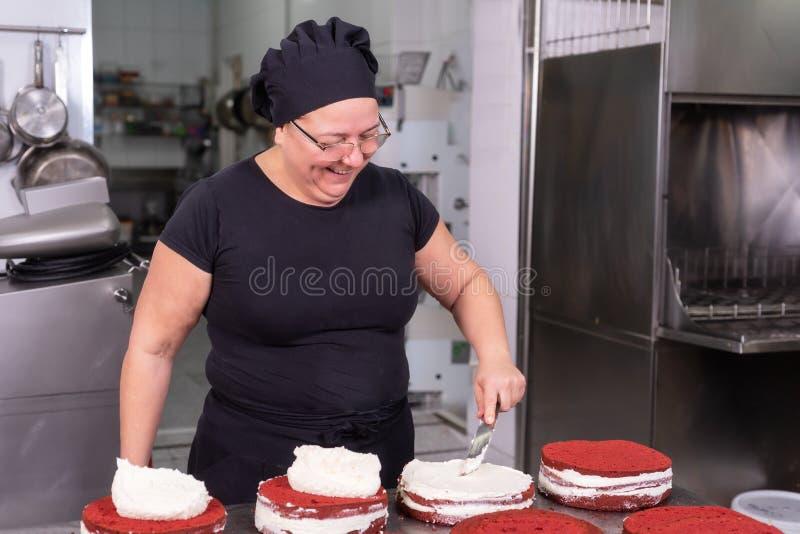 Frauenpatissier, der glücklich, Kuchen machend an der Konditorei lächelt und arbeitet lizenzfreies stockfoto