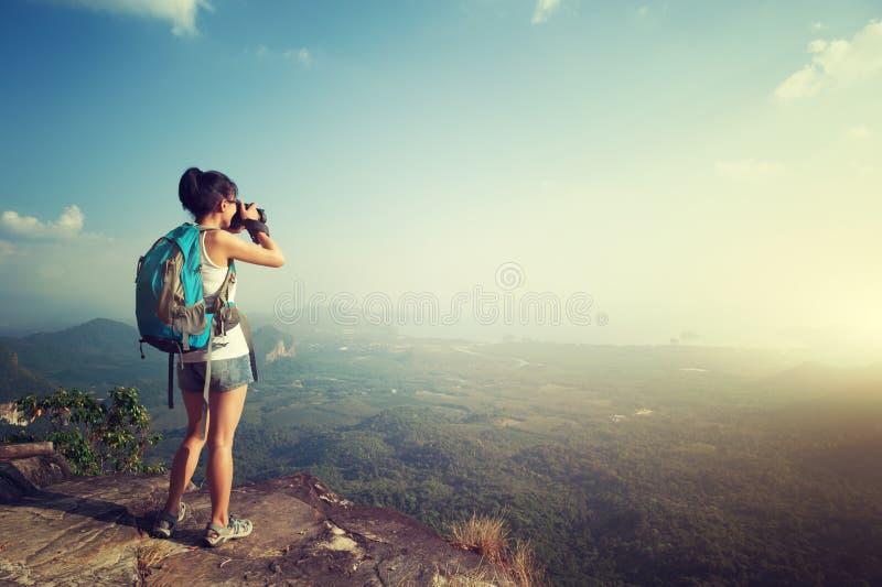 Frauenphotograph, der Foto an der Bergspitze macht stockbilder