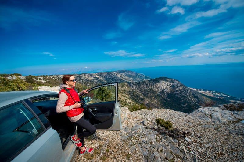 Frauenphotograph mit Auto auf die Oberseite des Berges stockfotos