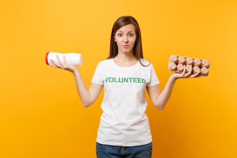 Frauenporträt im weißen T-Shirt mit schriftlichem Aufschriftgrüntitel freiwilliger Griff Plastikflasche, Pappschachtel lizenzfreie stockfotos