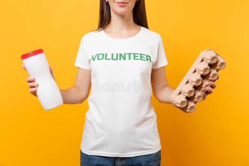 Frauenporträt im weißen T-Shirt mit schriftlichem Aufschriftgrüntitel freiwilliger Griff Plastikflasche, Pappschachtel lizenzfreies stockbild