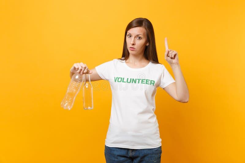 Frauenporträt im weißen T-Shirt mit schriftlicher Aufschrift grüner Titel freiwilliger Griff Plastik und Glasflaschen lokalisiert lizenzfreies stockbild
