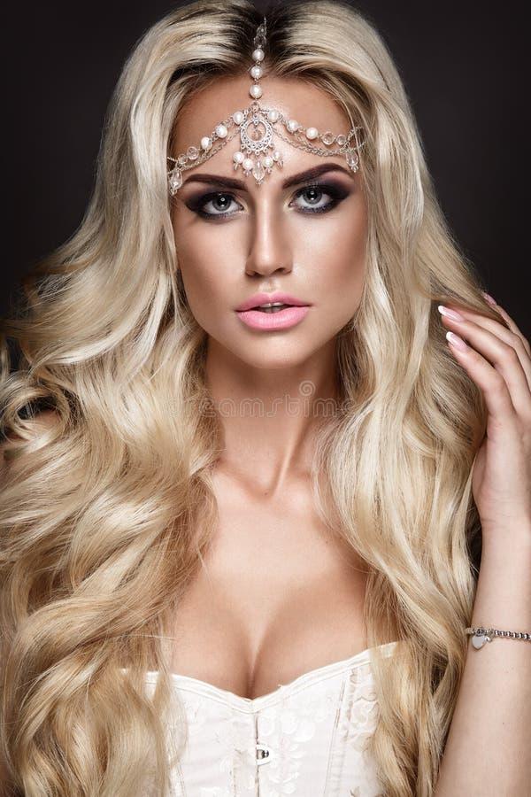 Frauenporträt lokalisiert auf dunklem Hintergrund Blondes junges Mädchen, das mit Schmuck auf Kopf aufwirft stockbilder