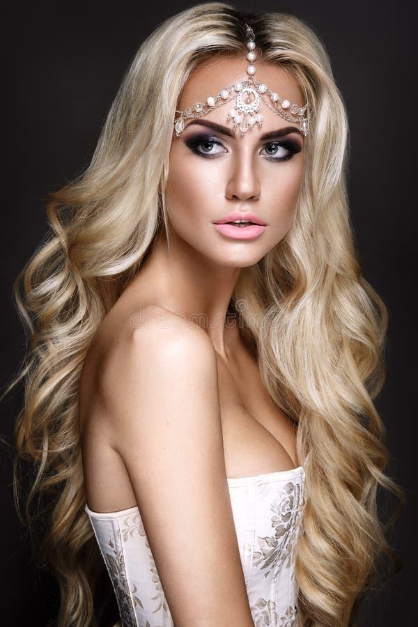 Frauenporträt lokalisiert auf dunklem Hintergrund Blondes junges Mädchen, das mit Schmuck auf Kopf aufwirft stockbild