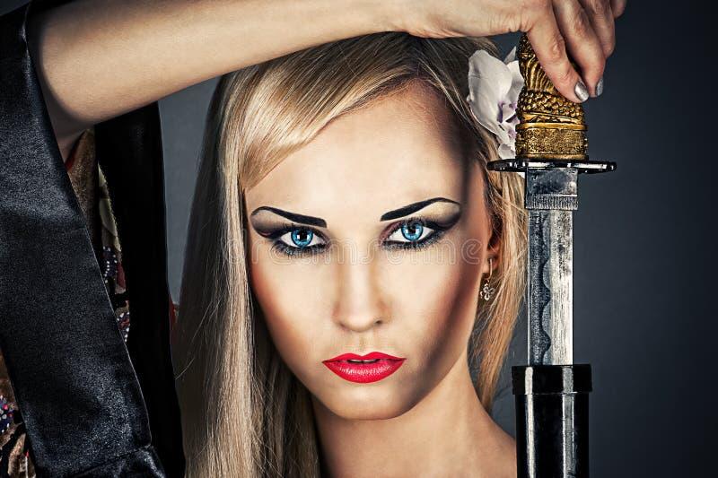 Frauenporträt mit einer Samuraiklinge lizenzfreie stockfotos