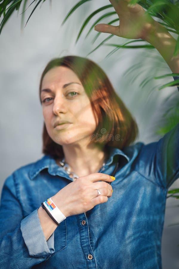 Frauenporträt mit grünen Blättern stockfoto