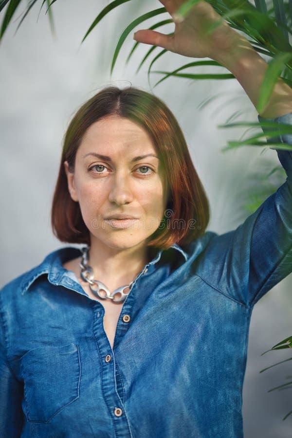 Frauenporträt mit grünen Blättern lizenzfreie stockbilder
