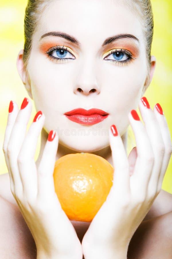 Frauenportrait, das eine orange Zitrusfrucht anhält stockfotografie
