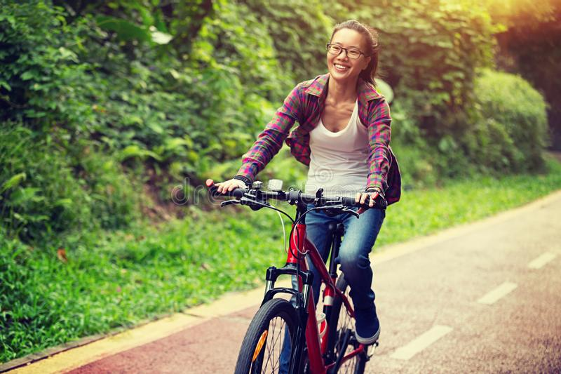Frauenradfahrer, der auf Schneise radfährt lizenzfreie stockfotos