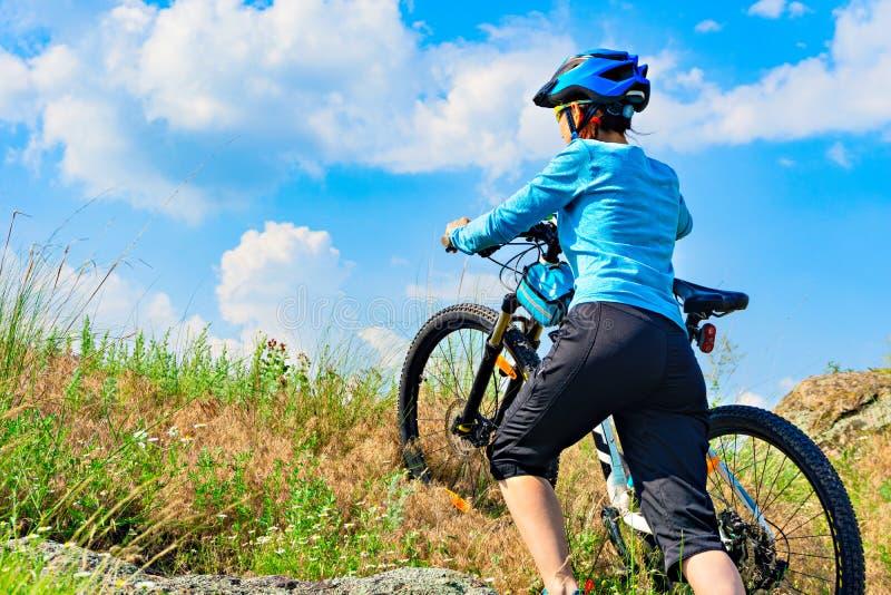 Frauenradfahrer, der ihr Fahrrad herauf eine steile Steigung drückt stockbild