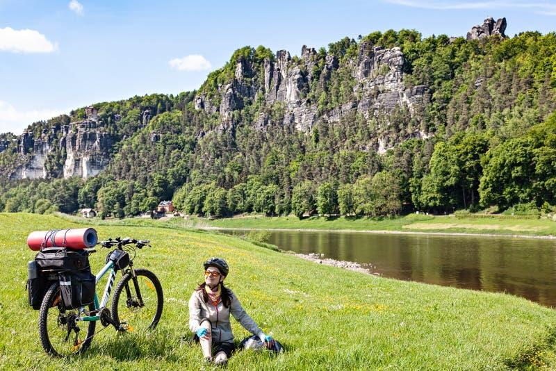 Frauenradfahrer mit dem geladenen Fahrrad, das Bruch beim Reisen hat stockfotografie