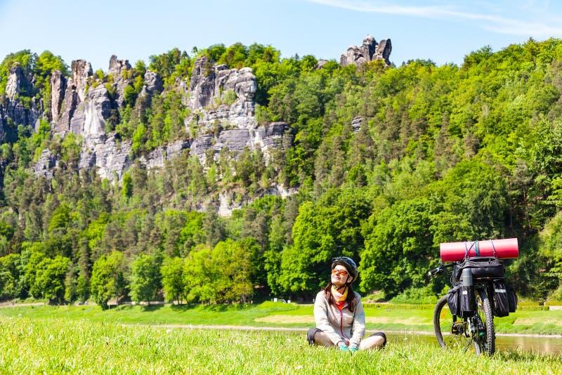 Frauenradfahrer mit dem geladenen Fahrrad, das Bruch beim Reisen hat stockbild