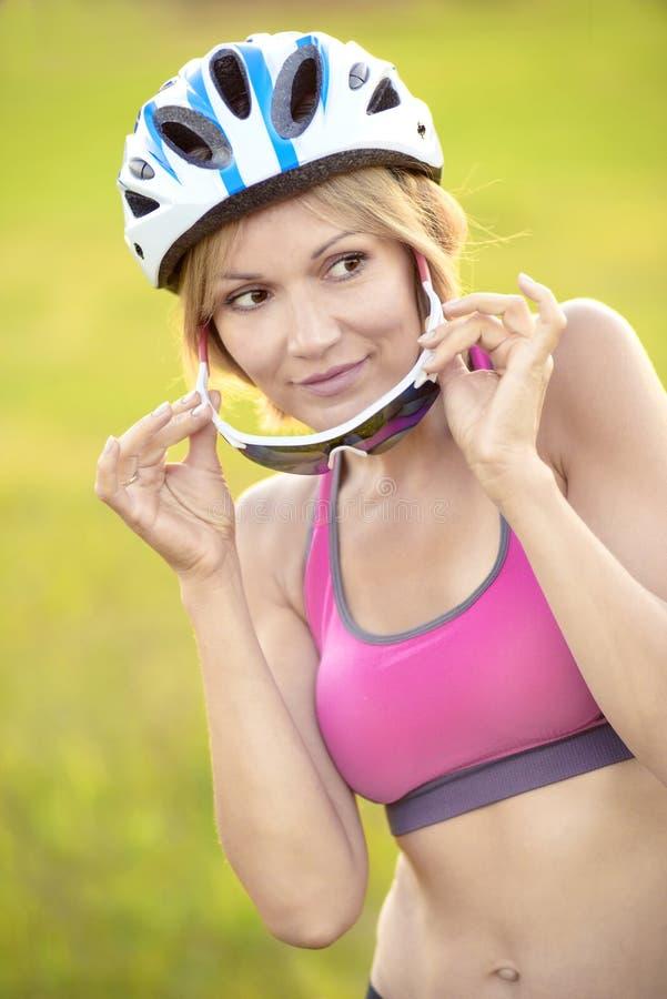 Frauenradfahrer vor dem hintergrund des grünen Grases lizenzfreies stockfoto