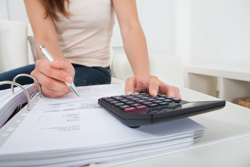 Frauenrechenausgangsfinanzen bei Tisch lizenzfreie stockfotos