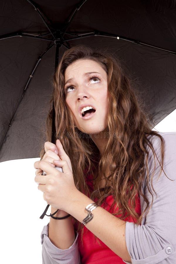 Frauenregenschirm, der oben frustriert schaut lizenzfreies stockbild