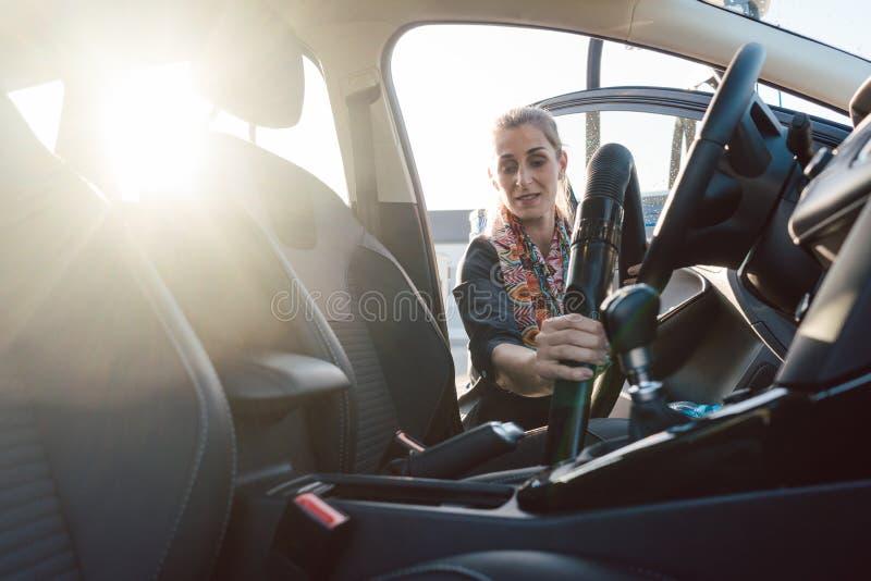 Frauenreinigung innerhalb des Autos stockfoto