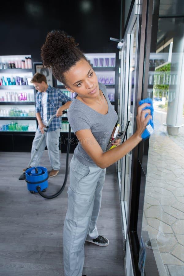 Frauenreinigungsfenster mit Lappen und Reiniger sprühen am Salon lizenzfreies stockfoto