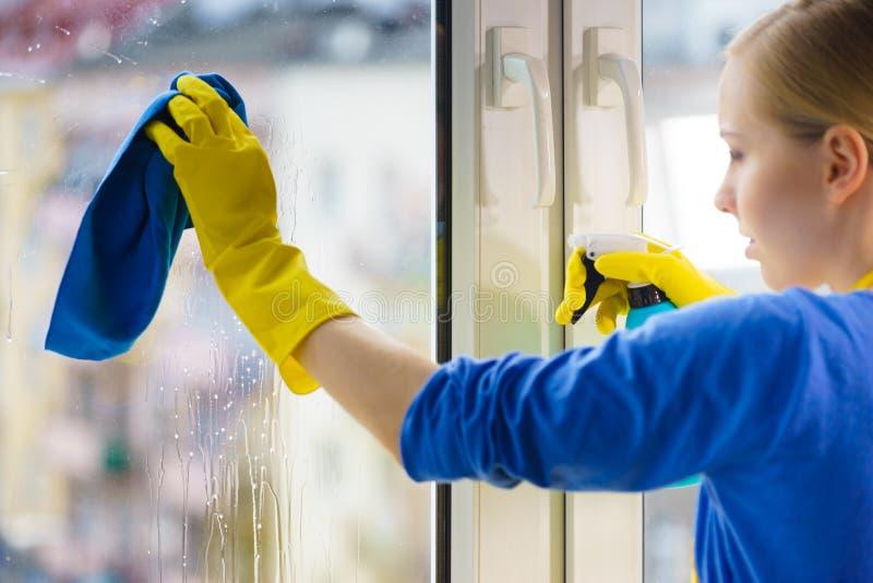 Frauenreinigungsfenster zu Hause lizenzfreie stockbilder