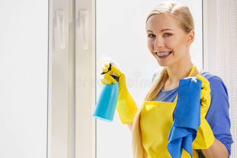Frauenreinigungsfenster zu Hause stockfoto