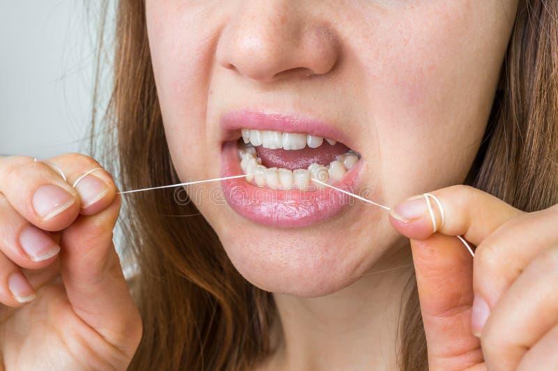 Frauenreinigungszähne mit Zahnseide lizenzfreies stockfoto