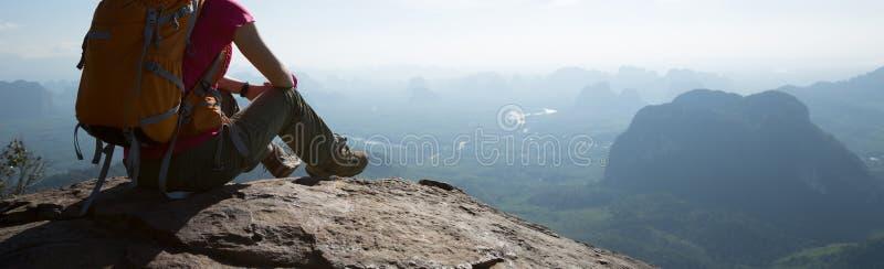 Frauenreisender, der auf Bergspitzeklippenrand sitzt stockbilder