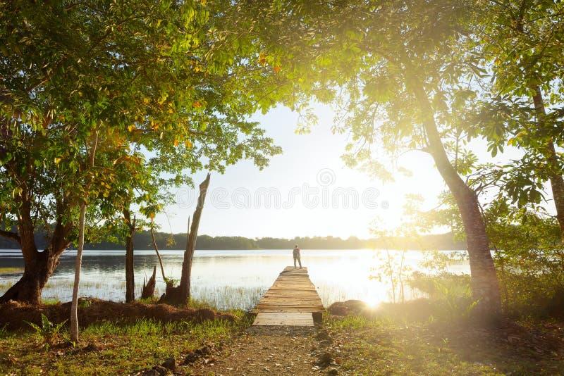 Frauenreisender, der auf dem Pier, schönen Sonnenuntergang Abo betrachtend steht stockbild