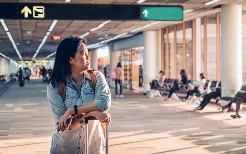 Frauenreisender, der aus Fenster heraus schaut und mit Koffern wartet stockfotografie