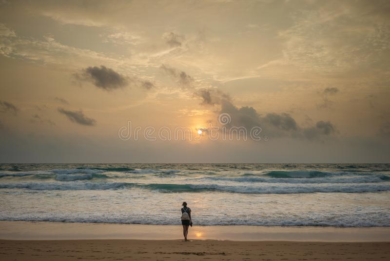 Frauenreisender, der im Abstand auf dem Strand steht und den Sonnenuntergang betrachtet stockbilder