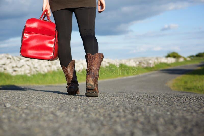 Frauenreisender, der mit roter Tasche geht stockfotografie
