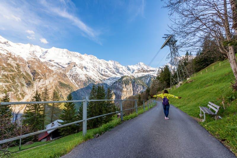 Frauenreisender, der zu den Bergen die Schweiz geht und schaut lizenzfreie stockbilder