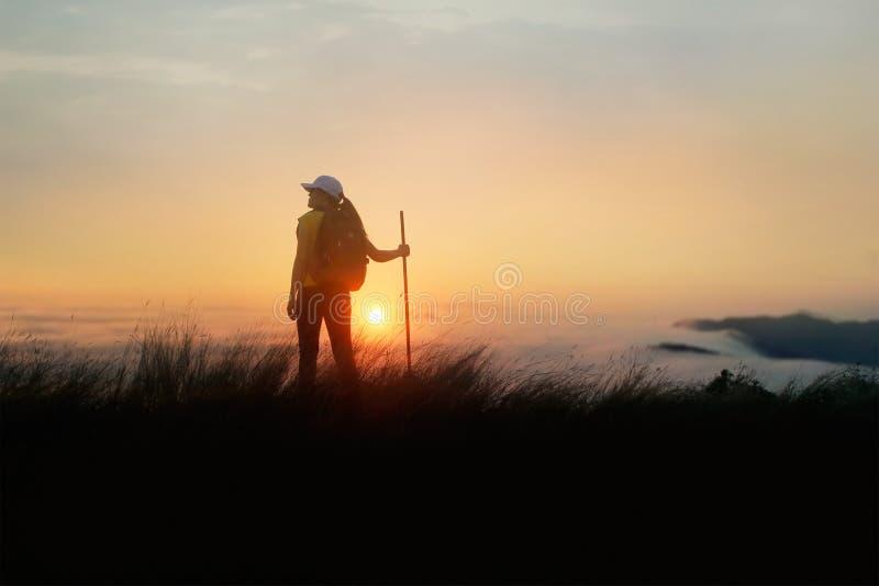 Frauenreisender mit dem Rucksack, der die aktiven Sommerferien des Abenteuers im Freien auf Höchsttalsonnenunterganghintergrund,  lizenzfreie stockfotos
