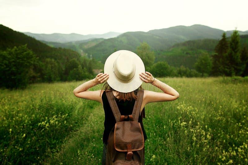 Frauenreisender mit dem Rucksack, der Hut hält und überraschend betrachtet lizenzfreies stockbild