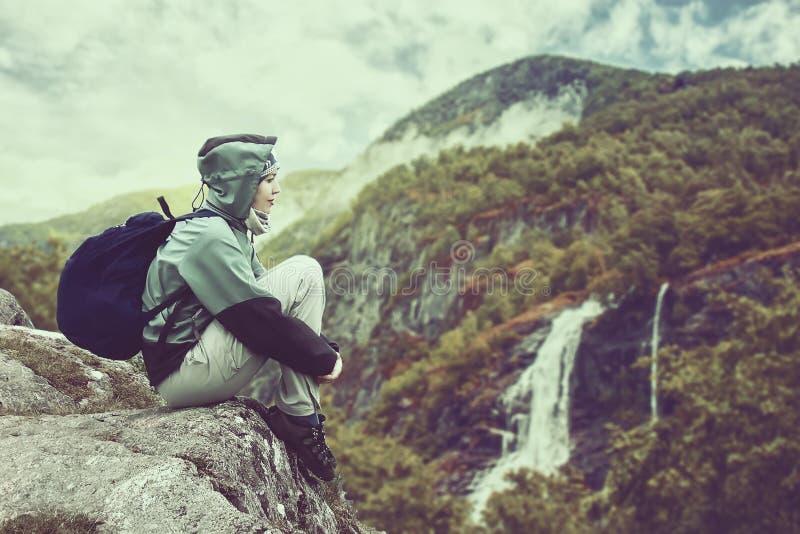 Frauenreisender mit dem Rucksack, der in Norwegen-Bergen mit ausgezeichnetem Wasserfall wandert lizenzfreies stockbild