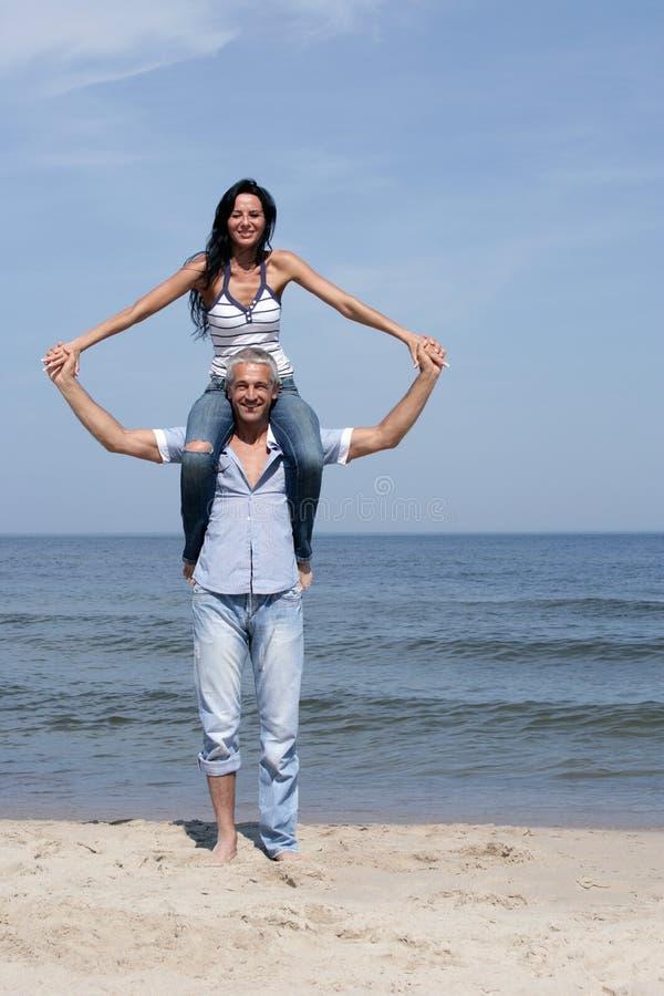 Frauenreiten auf Schultern des Mannes lizenzfreie stockfotos