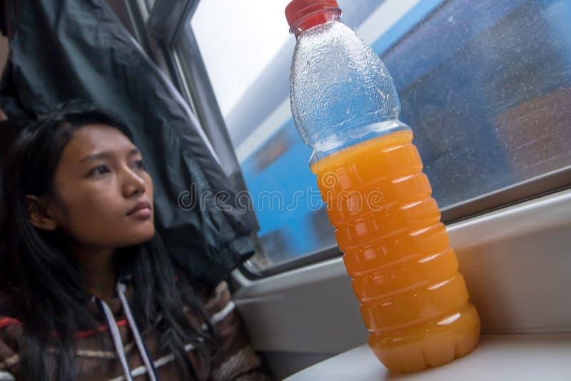 Frauenreiten durch Eisenbahn mit Orangensaft auf Tabelle stockfotografie