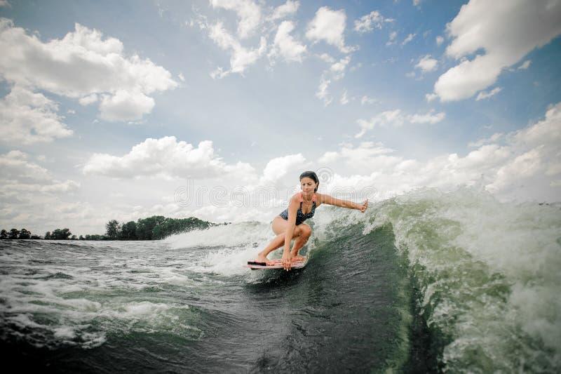 Frauenreiten-wakeboard auf der hohen Welle, die heraus Spray spiting ist stockbild