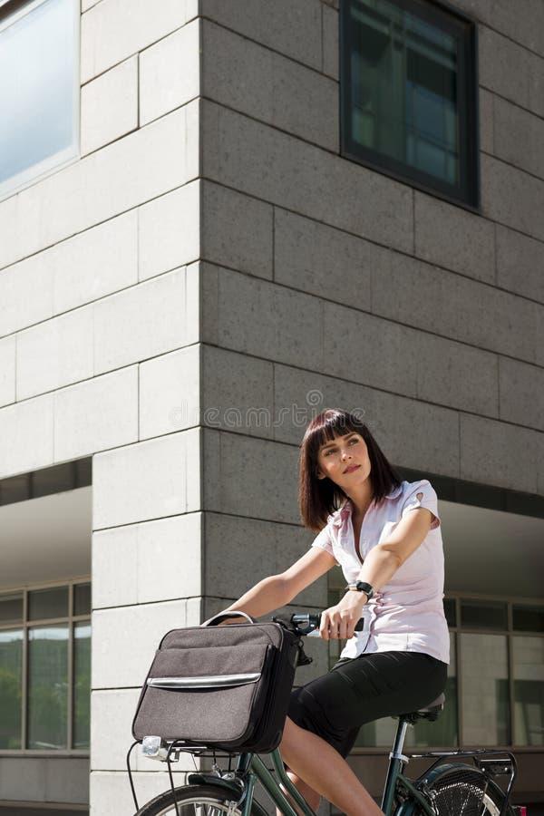 Frauenreitfahrrad und Gehen zu arbeiten stockbild
