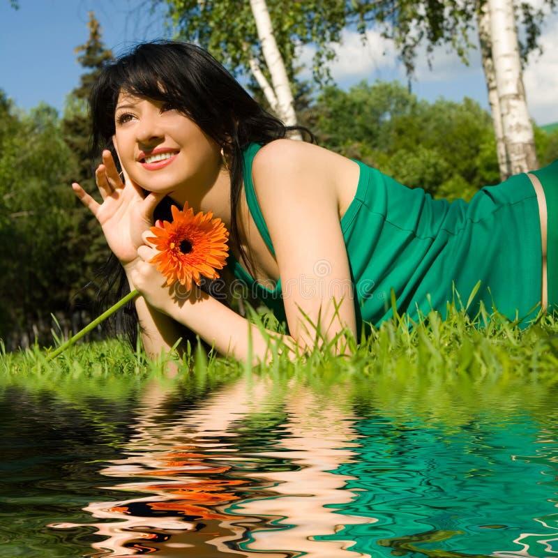 Frauenrest im Park mit Blume lizenzfreies stockbild