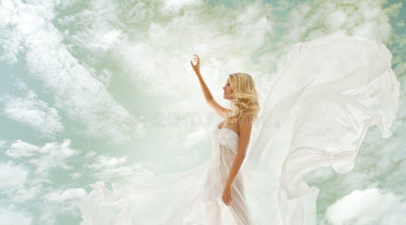 Frauenschönheit, Mädchen in flatterndem Kleid über Himmel lizenzfreie stockbilder
