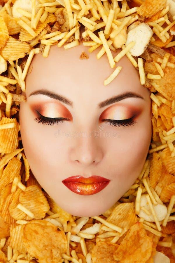 Frauenschönheits-Gesichtsopfer von unhealth Schnellimbiss-Kartoffelchi Essens lizenzfreies stockfoto
