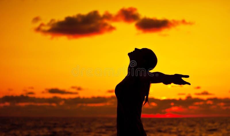 Frauenschattenbild über Sonnenuntergang lizenzfreies stockfoto