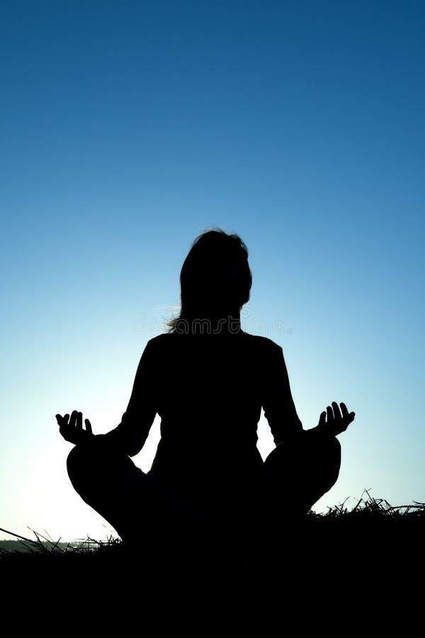 Frauenschattenbild, das Yoga bildet stockfoto
