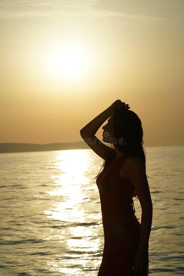 Frauenschattenbild durch Sonnenuntergang lizenzfreie stockfotografie