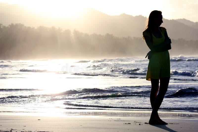 Frauenschattenbild durch Sonnenuntergang lizenzfreie stockbilder