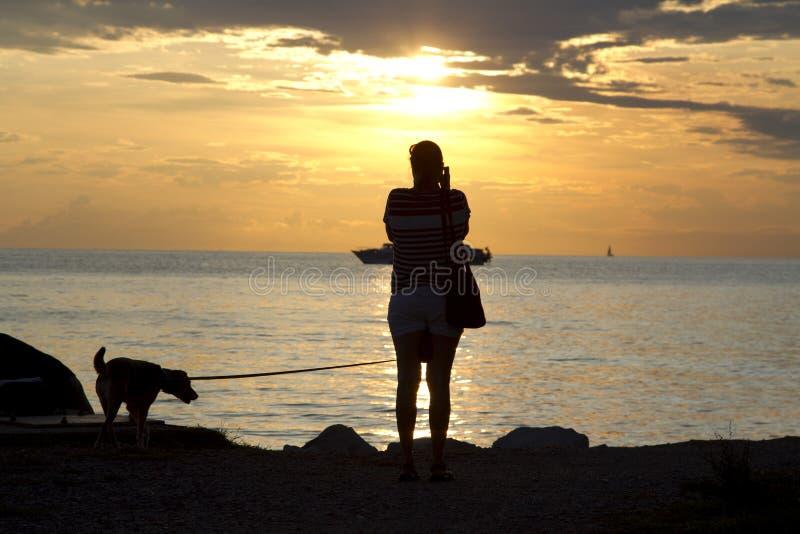 Frauenschießen mit Kamera bei Sonnenuntergang lizenzfreies stockbild
