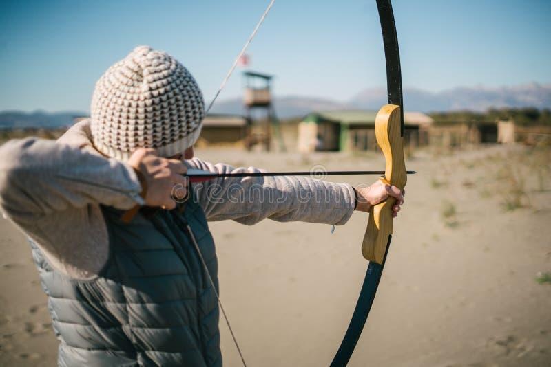 Frauenschießenziel mit ihrem Pfeil und Bogen an einem sonnigen Tag auf dem Strand lizenzfreie stockbilder