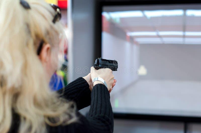 Frauenschießen im virtuellen Schießstand stockbilder